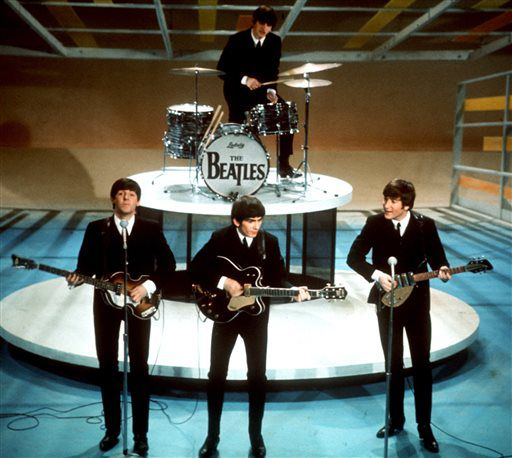 """FILE - In this Feb. 9, 1964 file photo, The Beatles perform on the CBS """"Ed Sullivan Show"""" in New York. They love us, yeah! yeah! yeah! At 12:01 a.m. local time on Dec. 24, 2015, around the world, the Beatles' music will be available for streaming from a wide range of outlets, a representative announced Wednesday, Dec. 23. (AP Photo, File)"""