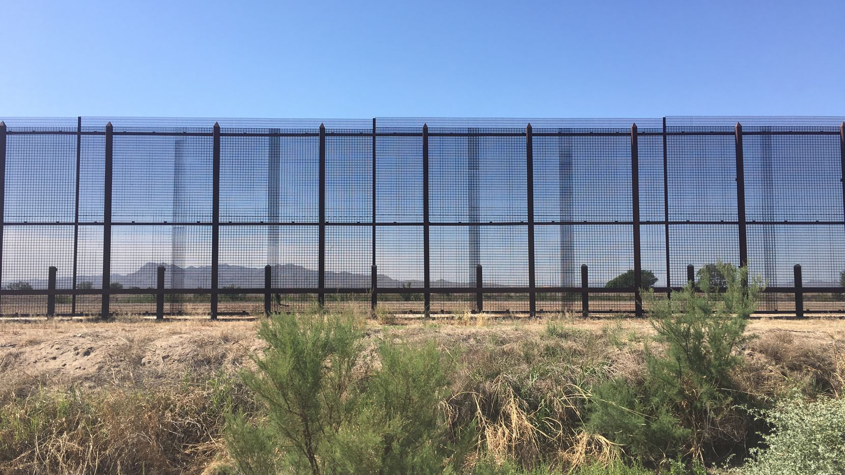 The border fence in Tornillo is on private land owned by a pecan farmer in West Texas. Mountains in Mexico are visible through the 18 foot fence.