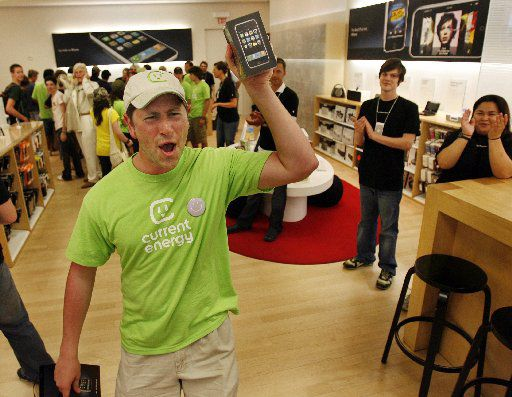 Ben Lack of Dallas celebrates as he leaves with the first iPhone ever sold at the Apple store on Knox Street in Dallas on July 29, 2007.