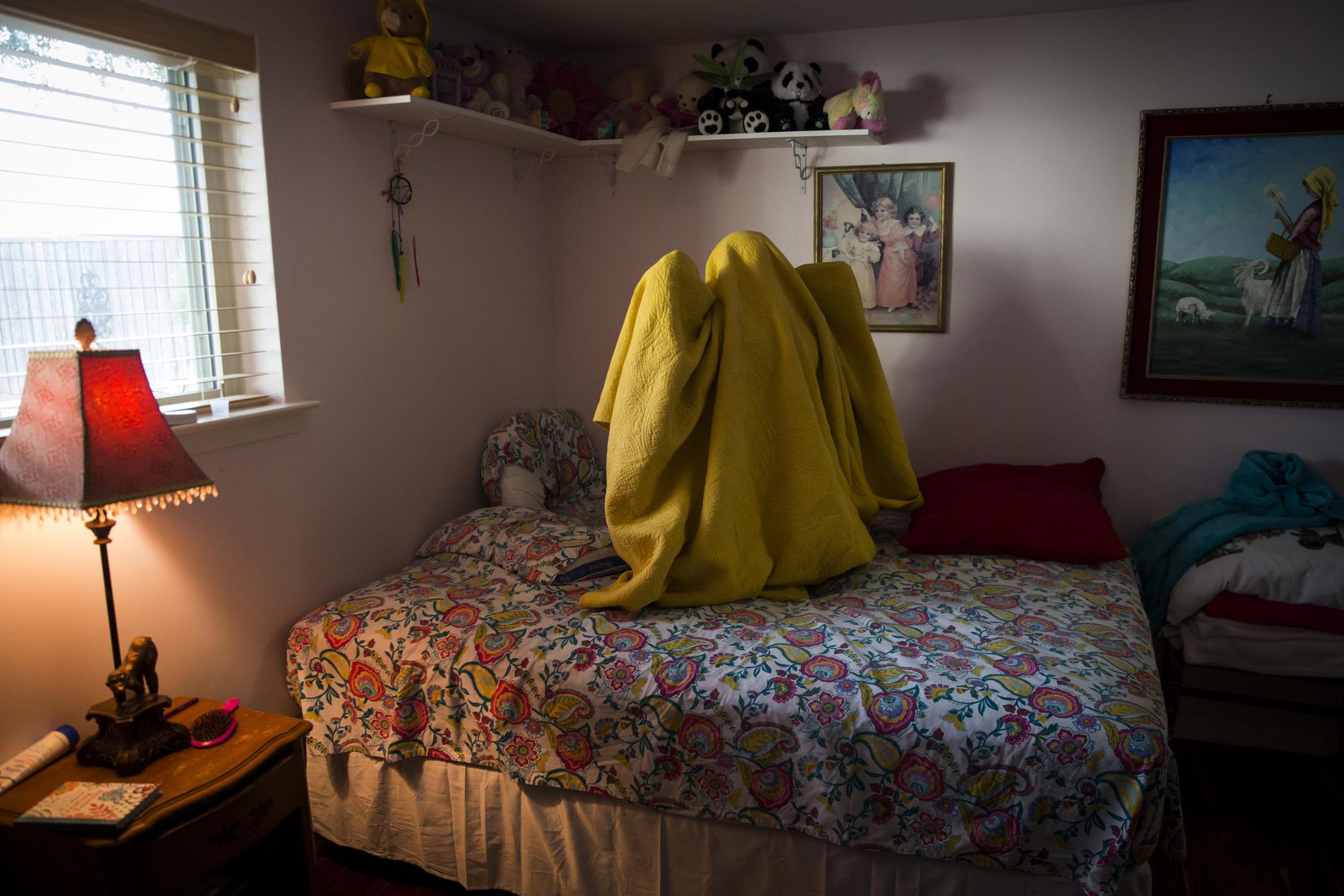 Kara Zartler wraps herself in her blanket, kneeling on her bed and rocking forward and back, one of her usual calming mechanisms, after getting home from school on Thursday, March 9, in Richardson. (Smiley N. Pool/The Dallas Morning News)