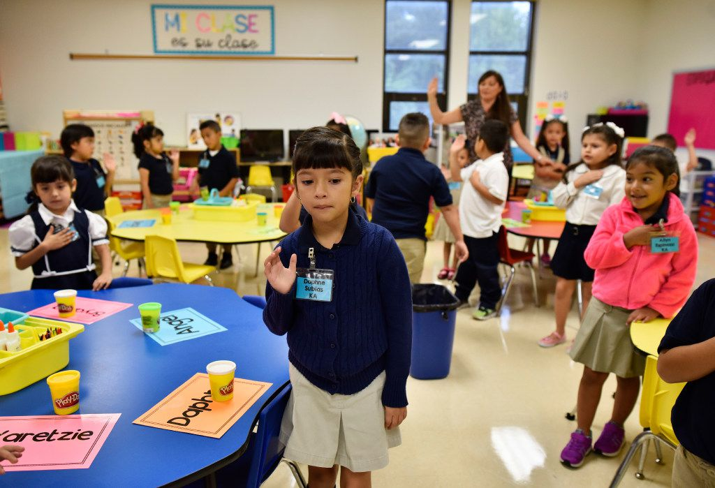 Daphne Subias raises her right hand with her classmates during the Pledge of Allegiance on the first day of school at Arturo Salazar Elementary school in Dallas on  Aug. 28.
