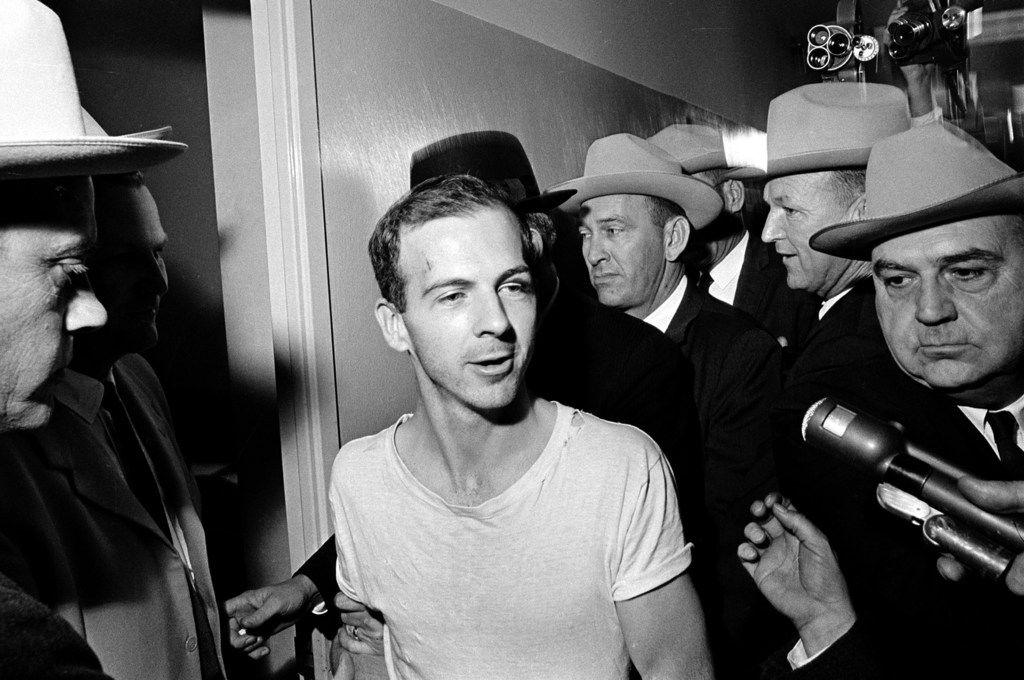 In this Nov. 23, 1963, file photo, surrounded by detectives, Lee Harvey Oswald talks to the media as he is led down a corridor of the Dallas police station. (AP Photo)