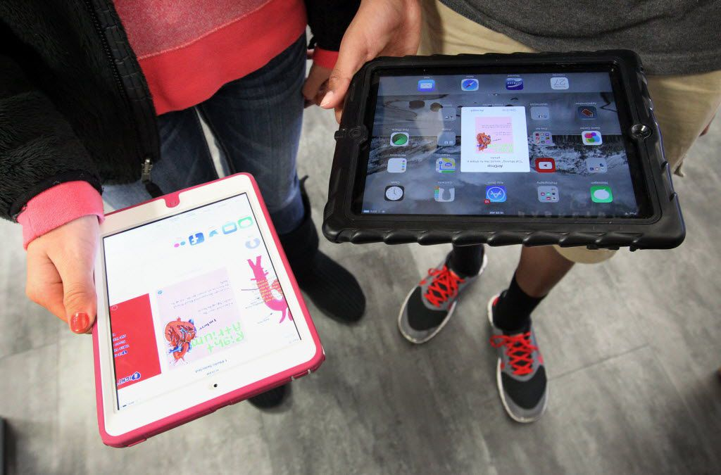 Seventh-grader Cat Moring (left) and eighth-grader Vivek Chilakamarri show how to share files using AirDrop in a classroom at Clayton Downing Middle School in Flower Mound in March, 2014. (Dallas Morning News File Photo)