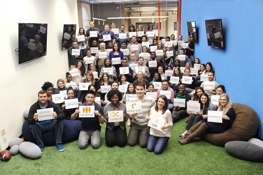 YourCause employees pose for a team photo. The cards represent things the company pledges to help its clients do.