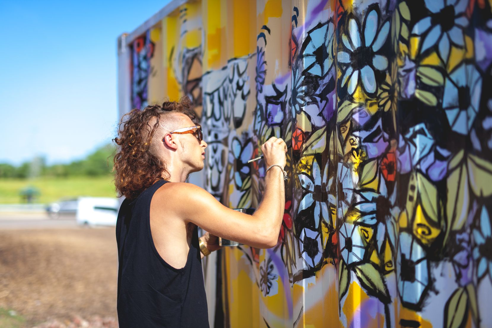 """Brinston paints his mural """"Bonton Blessing"""" at Bonton Farms in South Dallas. The mural is one of the first that will cover a white fence surrounding the property."""