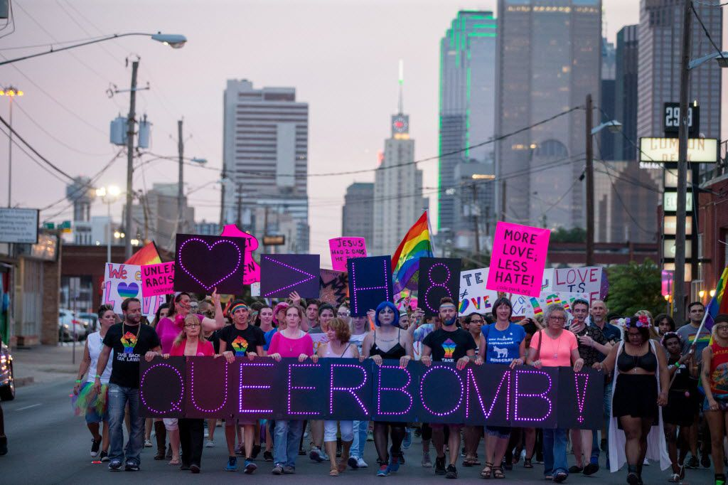 """Attendees of the Queer Bomb Dallas march down Commerce Street in Deep Ellum with LED signs that display """"Queer Bomb"""" on June 25, 2016 in Dallas. (Ting Shen/The Dallas Morning News)"""