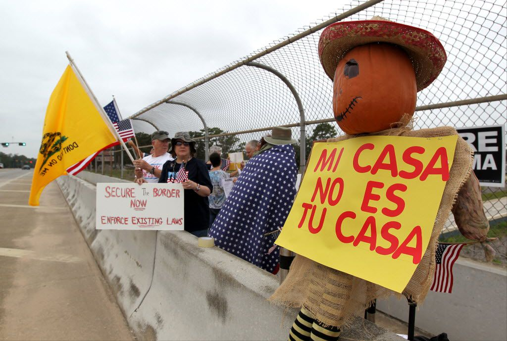 Protesters line the overpass during a protest against people who immigrate illegally,  July 19, 2014, in Conroe.