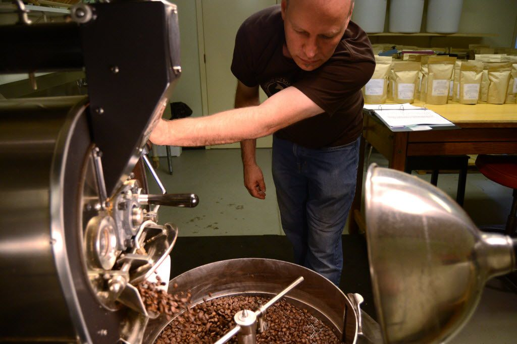 Kevin Sprague pours the roasted coffee beans into a cooling pan at Noble Coyote Coffee Roasters.