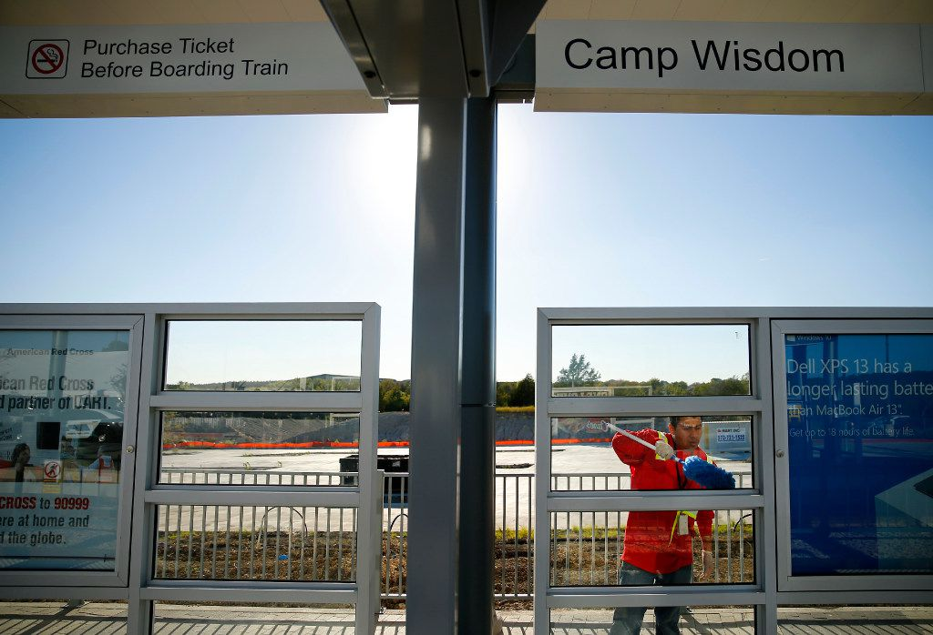 DART employee Eliezer Martinez cleans the newly constructed Camp Wisdom Station as it prepares to open Monday in southeast Oak Cliff.