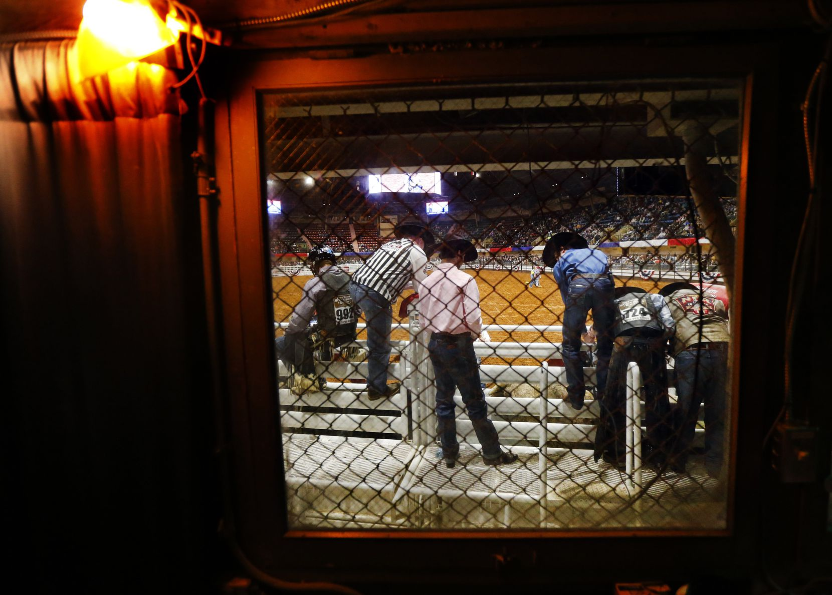 Bull riders on the bucking chutes are seen through the fence protected windows of the lower sound booth of Will Rogers Memorial Coliseum at the Fort Worth Stock Show and Rodeo in Fort Worth, Wednesday, January 30, 2019.