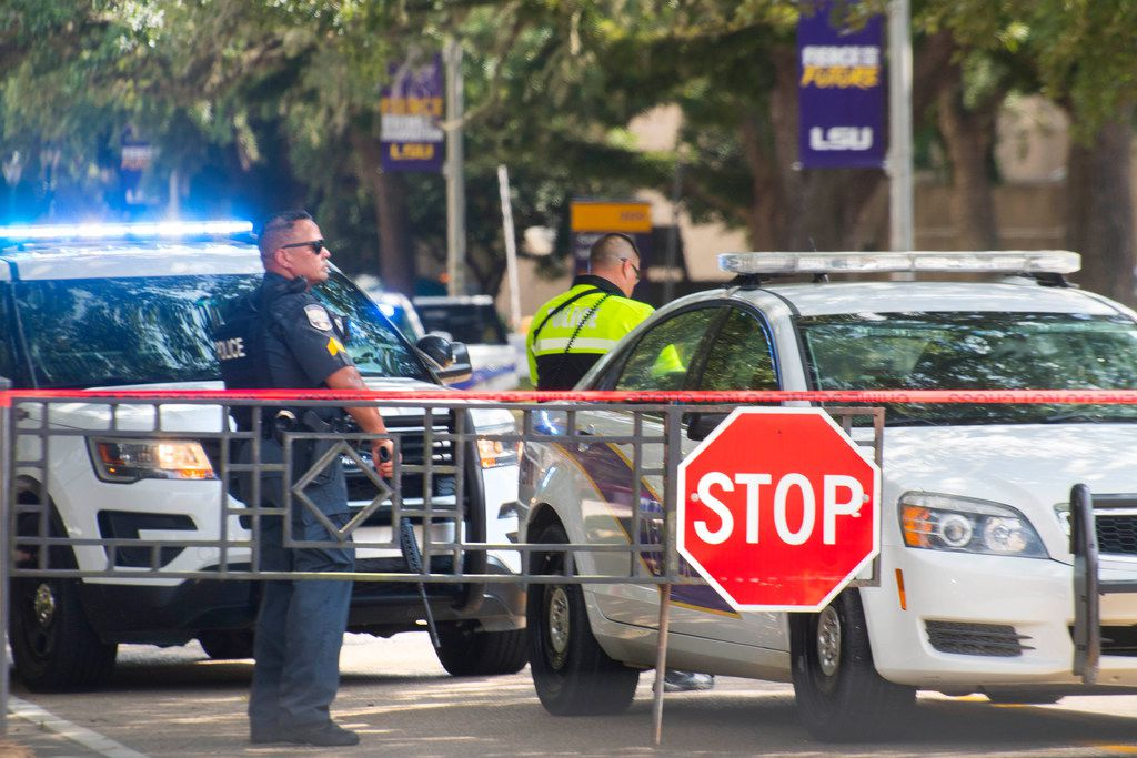 Law enforcement personnel stand with weapons near two LSU police vehicles parked between the LSU Student Union and Coates Hall after the all-clear on a possible armed intruder in Coates Hall on Tuesday, Aug. 20, 2019.