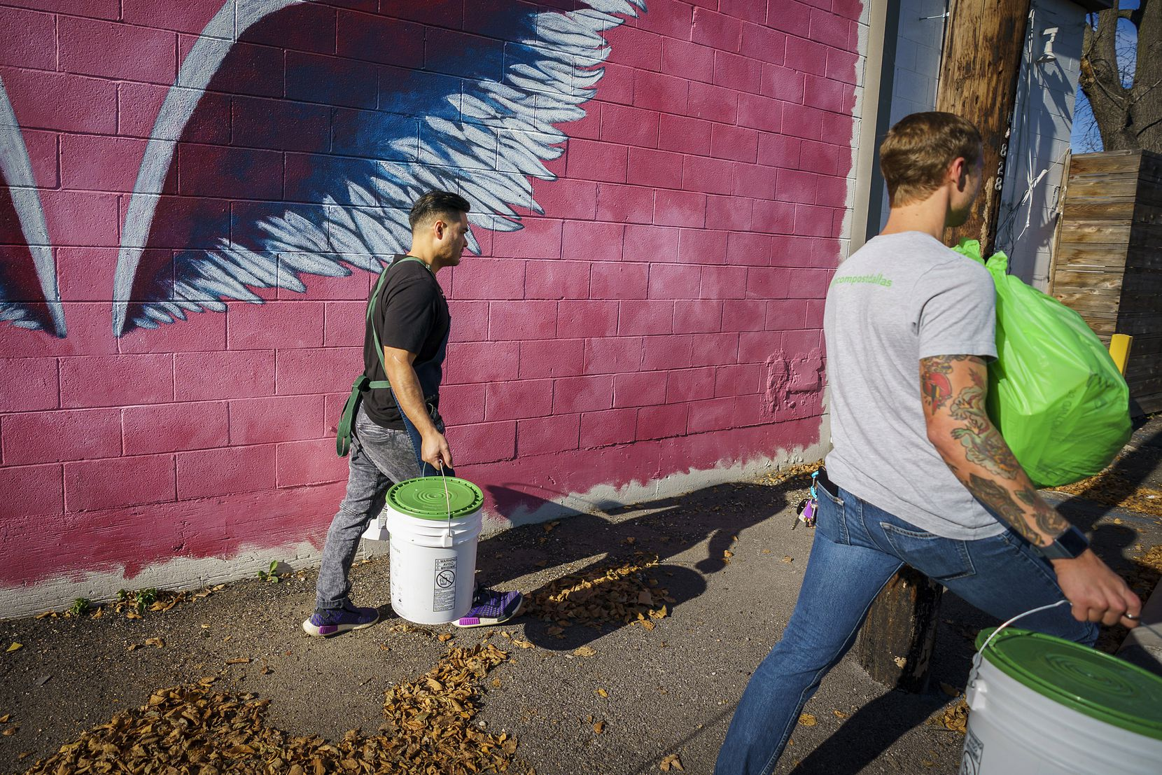 Donny Sirisavath (left), the chef and owner of Khao Noodle Shop, helps Wes Fitch of Turn Compost carry full buckets and bags of compostable materials to his vehicle during a pickup at the restaurant on Monday, Nov. 25, 2019, in Dallas. Turn Compost is a DFW-startup offering a service to pick up buckets compostable items that would otherwise end up in a landfill. (Smiley N. Pool/The Dallas Morning News)