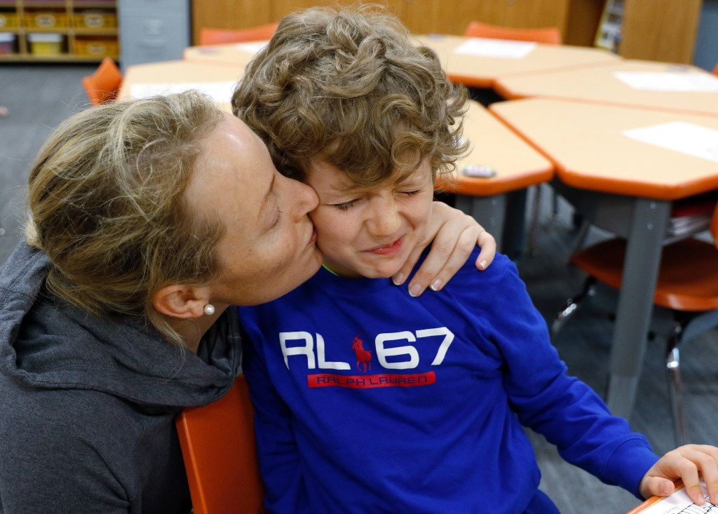 Christina Benedetti gives a goodbye kiss her son, Sebastian Benedetti, 7, as she leaves him at University Park Elementary.