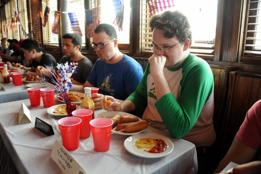 Mackenzie Nolan eats corn dogs at the 7th annual Brass Knuckles Corn Dog Beatdown at The Libertine Bar on July 4, 2015.
