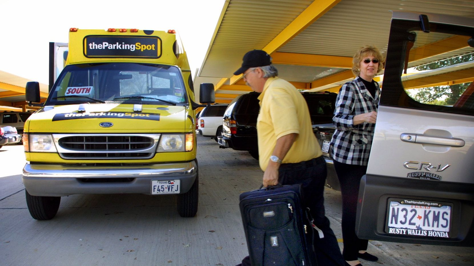 The Parking Spot driver James Rogers helps Deborah Grotke of Dallas load her bags onto a shuttle at the company's lot near DFW International Airport.