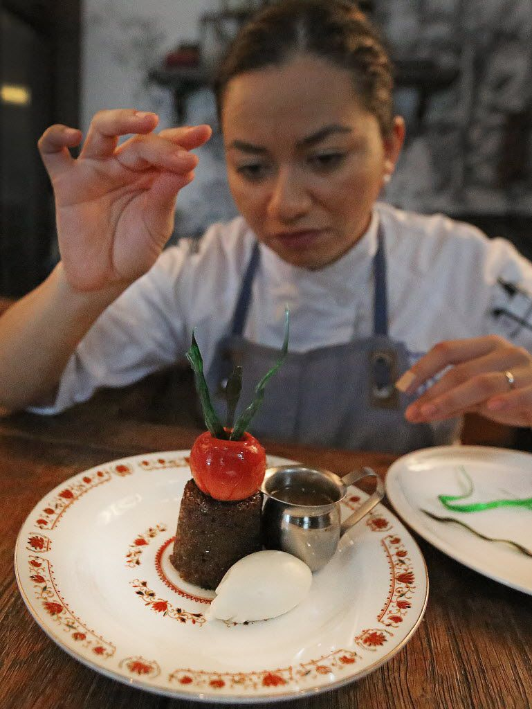 Pastry chef Marlene Duke puts the finishing touches on a toffee cake with crab apple.