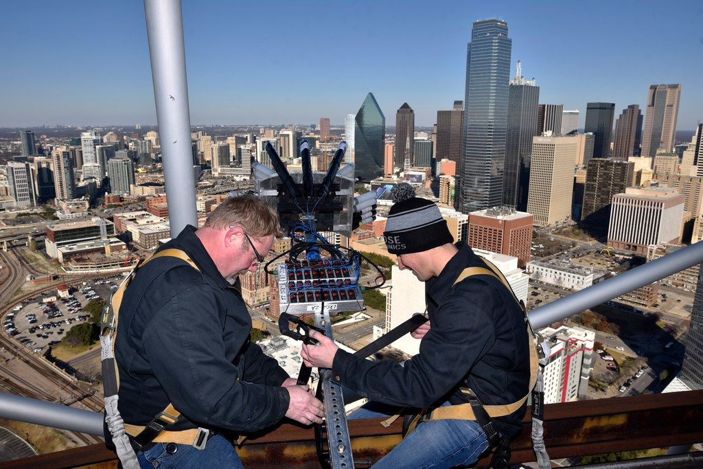 Pyrotechnicians Randy Linn (left) and Mike Cartolano of Melrose Pyrotechnics sit on beams near the edge of Reunion Tower as they install fireworks for this year's New Years Eve celebration.