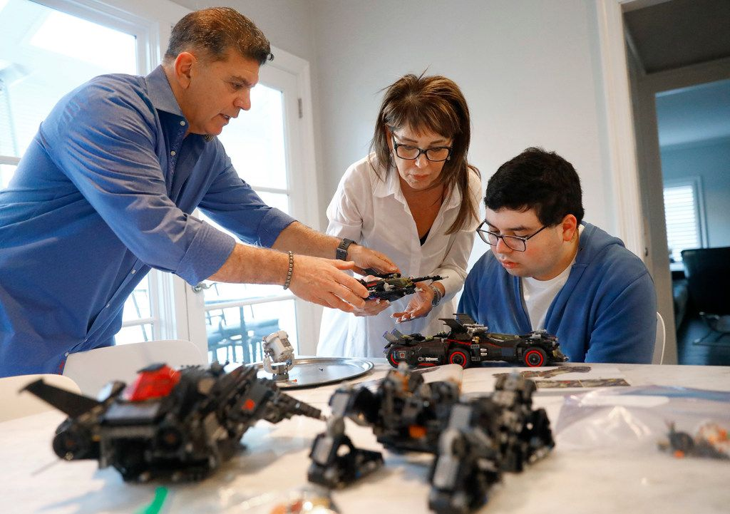 Mitch Basson lends a helping hand to his wife, Ingrid, and 17-year-old-son, Sam, as they finished constructing a Batmobile from Legos at their Dallas home. The Bassons moved to Texas from the Chicago area six months ago after reading about the 29 Acres program planned in Cross Roads.