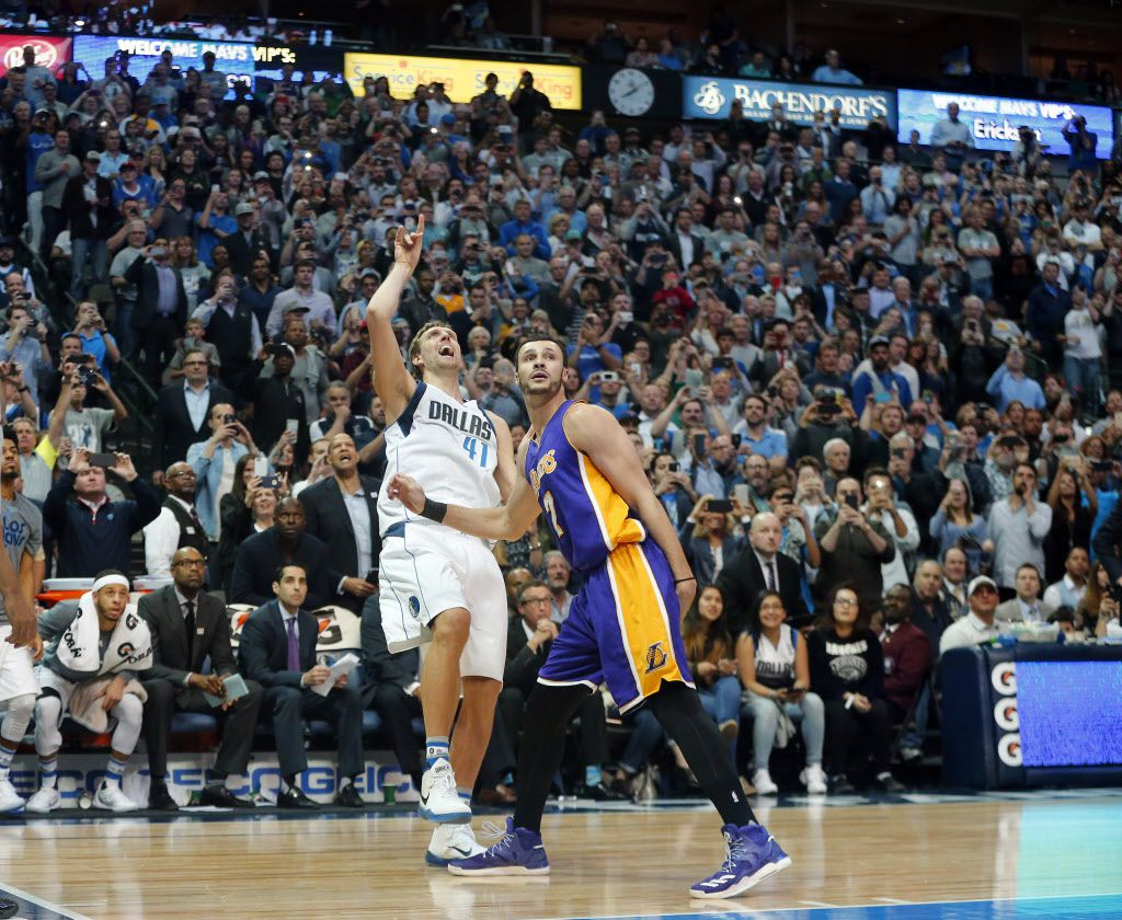 In front of his own bench, Dallas Mavericks forward Dirk Nowitzki (41) shoots and makes his 30,000 point against Los Angeles Lakers forward Larry Nance Jr. (7) in the second quarter at the American Airlines Center in Dallas, Tuesday, March 7, 2017. Dirk is only the 6th player in NBA history to reach the milestone. (Tom Fox/The Dallas Morning News )