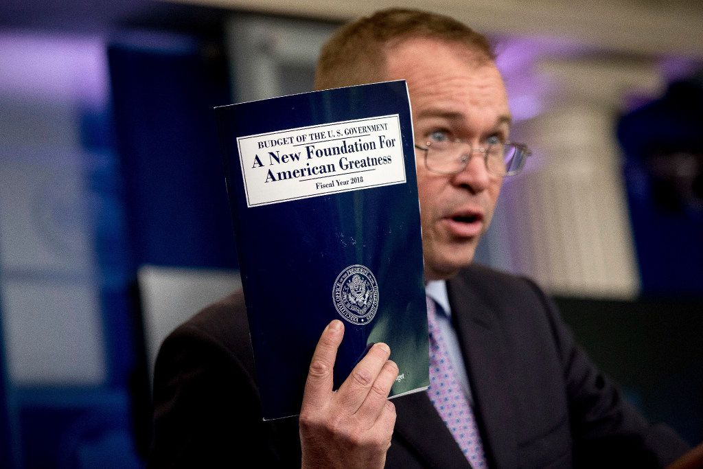 In this May 23, 2017, photo, Budget Director Mick Mulvaney holds up a copy of President Donald Trump's proposed fiscal 2018 federal budget as he speaks to members of the media at the White House.