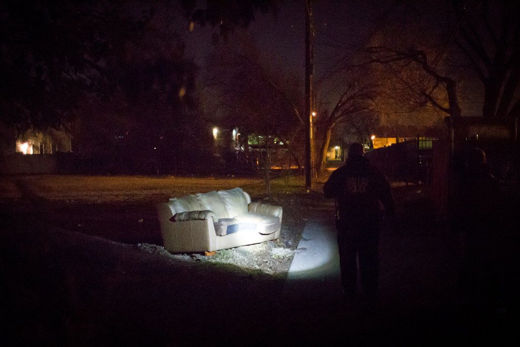 Dallas police Sgt. Keitric Jones shines a flashlight toward a sofa in a vacant lot along Bryan St. near Bennett Ave. during the annual homeless census on Thursday, Jan. 26, 2017, in Dallas.