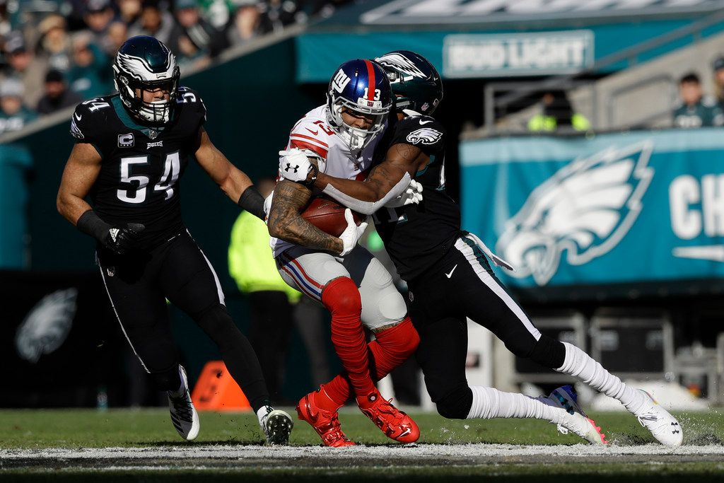 Philadelphia Eagles cornerback DeVante Bausby, right, tries to stop New York Giants wide receiver Odell Beckham (13) as Eagles Kamu Grugier-Hill (54) looks on during the first half of an NFL football game, Sunday, Nov. 25, 2018, in Philadelphia. (AP Photo/Michael Perez)