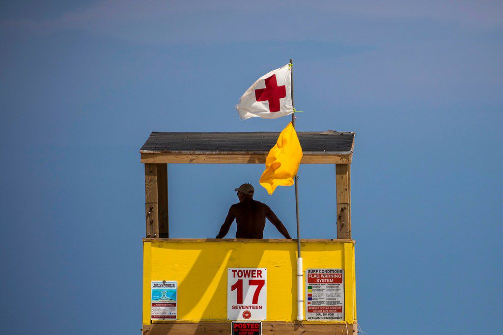 A beach guard looks out from a tower along Port Aransas Beach. Officials say day-trippers driving from as far away as San Antonio have sustained the town as it recovers from the devastation wrought when Hurricane Harvey hit the Texas Gulf Coast in August 2017.