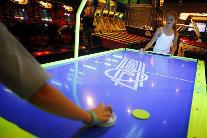Allison Boyd (right), 9, plays air hockey against her 10-year-old brother, Bobby Boyd, at Main Event in Frisco.