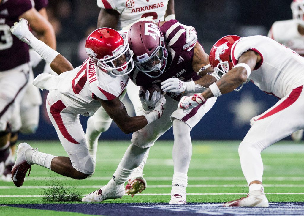 Texas A&M player is tackled by Arkansas Razorbacks defensive back Kevin Richardson II (30) and defensive back Santos Ramirez (9) during the fourth quarter of an NCAA football game between Texas A&M and Arkansas on Saturday, September 29, 2018 at AT&T Stadium in Arlington, Texas. (Ashley Landis/The Dallas Morning News)