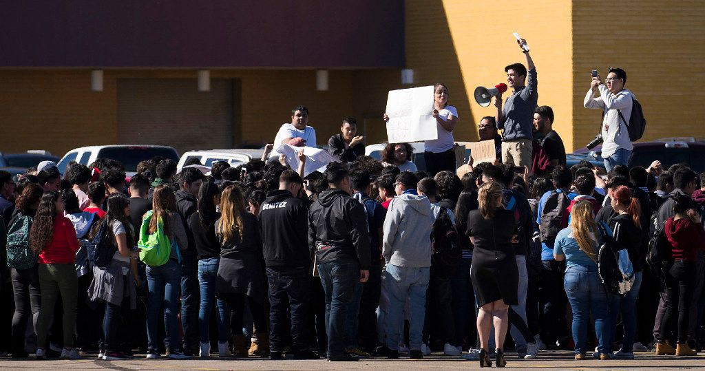 "Students at Moises E. Molina High School walk out of class and rally in the parking lot in support of ""A Day Without Immigrants,"" Thursday, Feb. 16, 2017, in Dallas. Immigrants around the U.S. stayed home from work and school to demonstrate how important they are to America's economy, and many businesses closed in solidarity, in a nationwide protest Thursday called A Day Without Immigrants. (Smiley N. Pool/The Dallas Morning News via AP)"