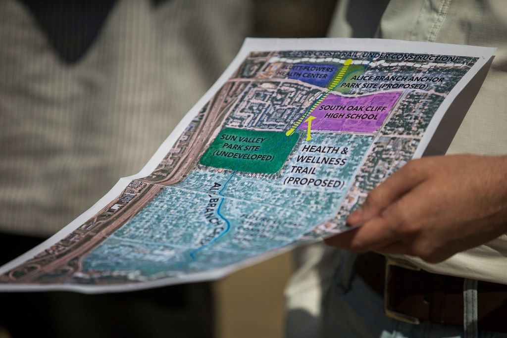 Robert Kent of The Trust for Public Land holds a map showing where the parks and trails would go along Five Mile Creek, an area littered with tires, empty liquor bottles and other trash.