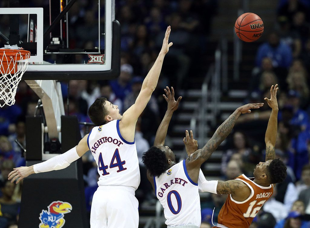 KANSAS CITY, MISSOURI - MARCH 14:  Kerwin Roach II #12 of the Texas Longhorns shoots over Marcus Garrett #0 and Mitch Lightfoot #44 of the Kansas Jayhawks during the quarterfinal game of the Big 12 Basketball Tournament at Sprint Center on March 14, 2019 in Kansas City, Missouri. (Photo by Jamie Squire/Getty Images)