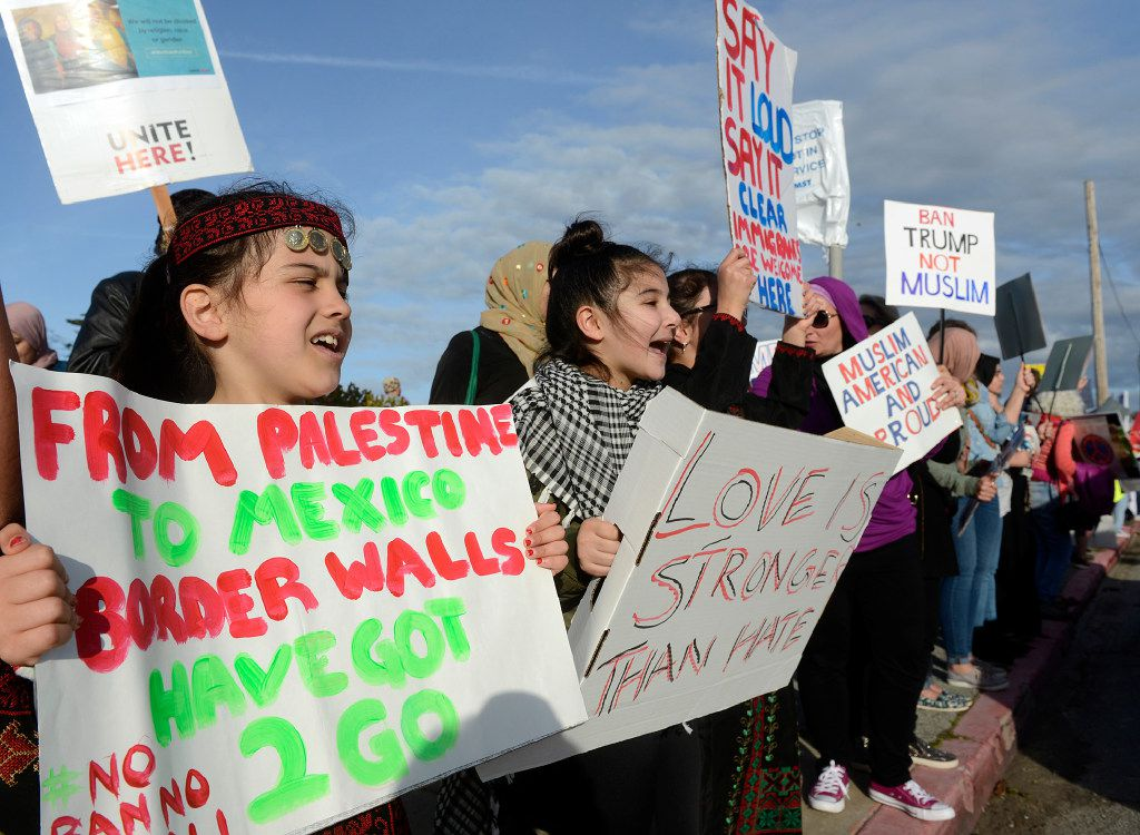 Monterey Muslim Community members Miriam Khalil, 7, left, and her friend Yasmin Melhem, 10, join others during a protest against President Donald Trump's travel ban, in Monterey, Calif., Saturday Feb. 4, 2017. (David Royal/The Monterey County Herald via AP)