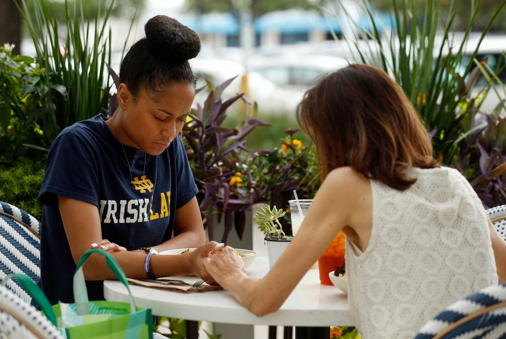 Cameasha Turner (left) prays with Cathey DeRouen, her third-grade teacher, before eating lunch in Dallas on Wednesday. Turner graduated from Lincoln High School and went on to the University of Texas at El Paso before getting a law degree at the University of Notre Dame.