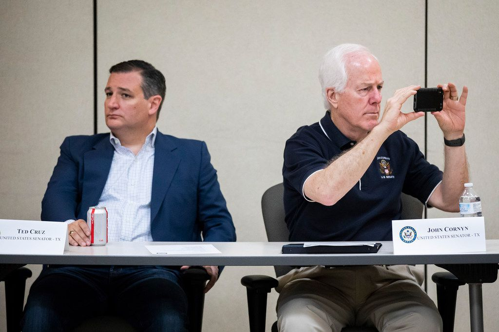 Senator John Cornyn takes photos with his phone as he and Senator Ted Cruz sit at the head of the table during a roundtable discussion at the Weslaco Border Patrol Station on Friday, June 22, 2018, in Weslaco, Texas. The Texas Senators held the roundtable with representatives of federal agencies, non-profits and local elected officials involved in handling immigrant families.