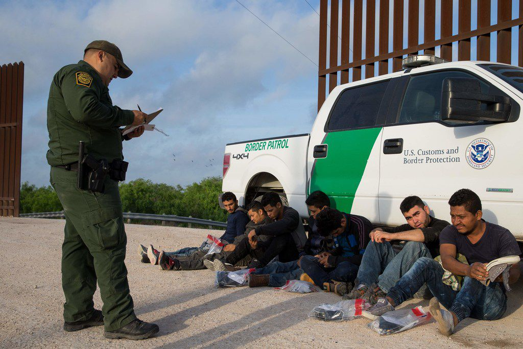 A Border Patrol agent apprehends immigrants entering the country illegally shortly after they crossed the border from Mexico into the United States in the Rio Grande Valley Sector near McAllen earlier this year.