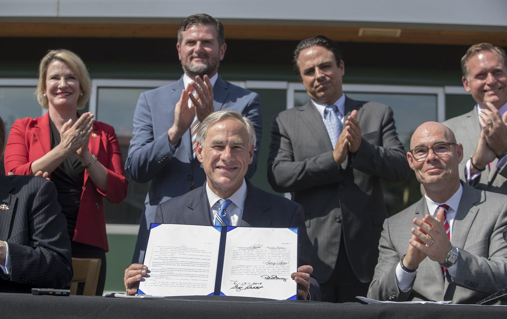Governor Greg Abbott outside of Wally's Burger Express in  Austin is surrounded by state legislators as he signs a bill that limits property tax growth, Wednesday, June 12, 2019.
