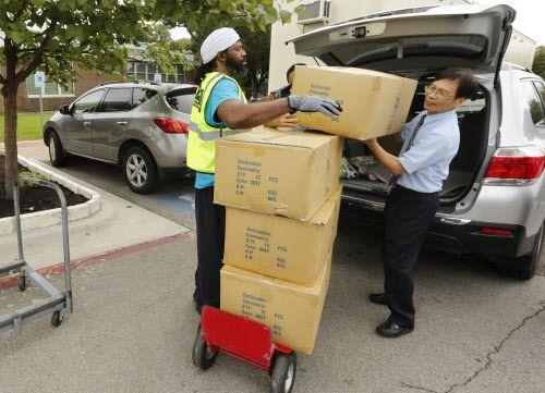 El voluntario Cason Bey, ayuda a Yeou Lil Lin Chi Li, de la Fundación Budista Tzu Chi con sábanas para los evacuados de Harvey en el centro Walnut Hill.