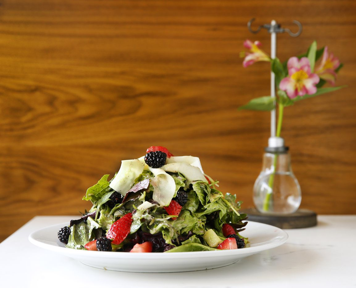 The Bella Berry Salad according to the menu is made with vibrant spring mix, nutty arugula & crunchy romaine tossed together with fresh sliced strawberries, blackberries, pistachios & crushed raspberry vinaigrette; finished with shaved cucumbers ribbons & microgreens at Bellagreen.
