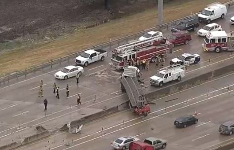 An 18-wheeler dangled over the edge of a barrier on Interstate 635 in Lake Highlands on Friday morning.
