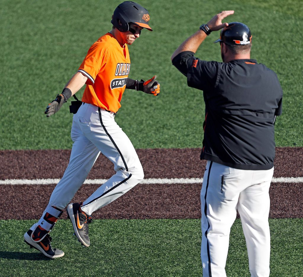 Oklahoma State's Hueston Morrill (1) reaches out to assistant coach James Vilade after hitting a home run during the fifth inning against Texas Tech in Game 2 of an NCAA college baseball tournament super regional Saturday, June 8, 2019, in Lubbock, Texas. (AP Photo/Brad Tollefson)