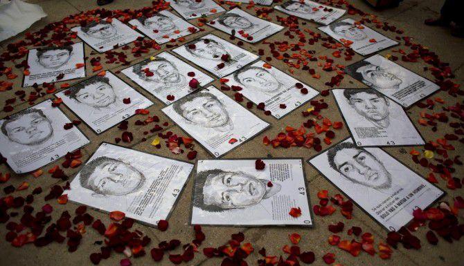 Dibujos de algunos de los 43 estudiantes desaparecidos en Guerrero, durante una protesta en la Ciudad de México. (AP/REBECCA BLACKWELL)