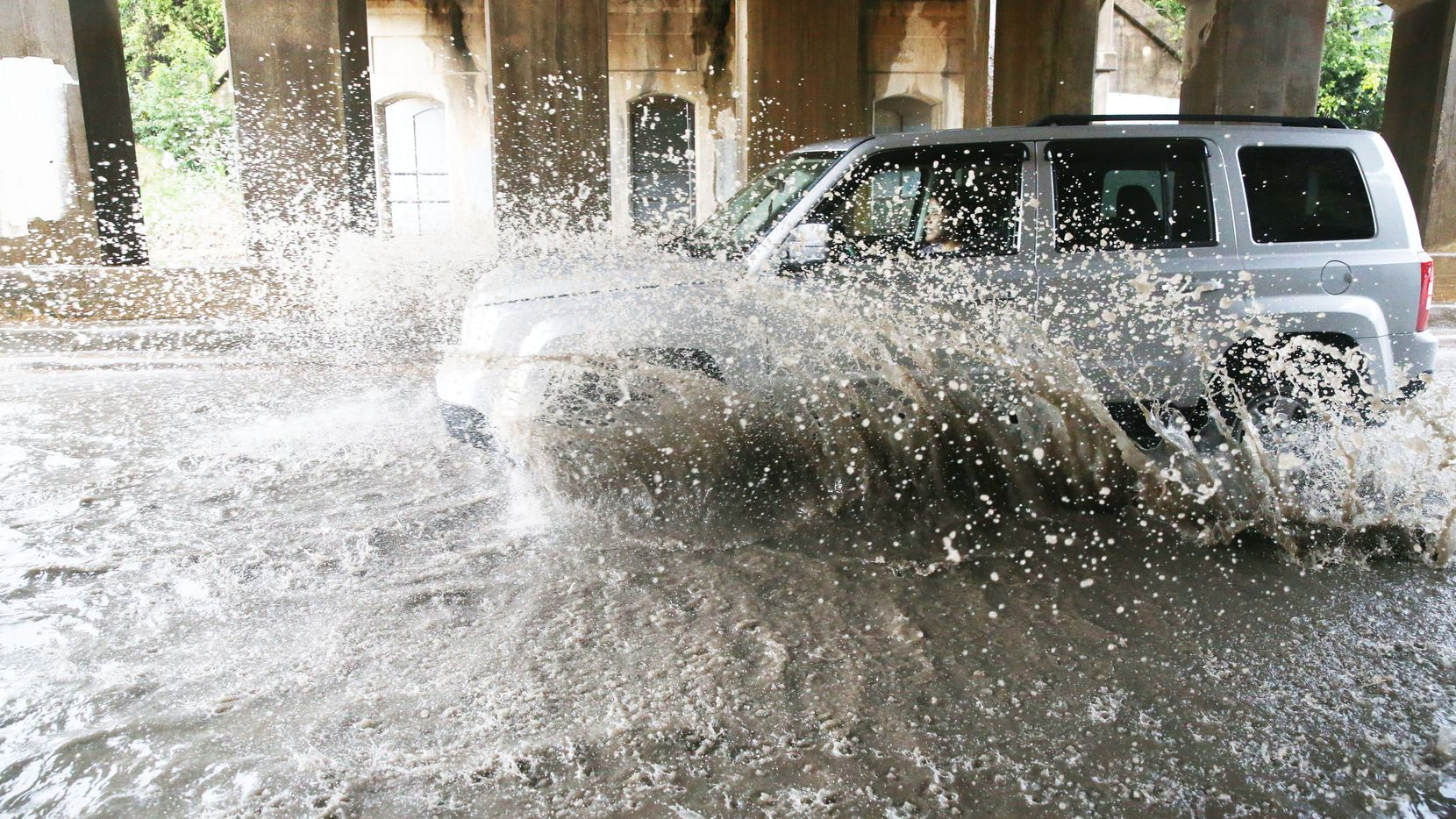A car drives through standing water at 2400 Sylvan Ave.