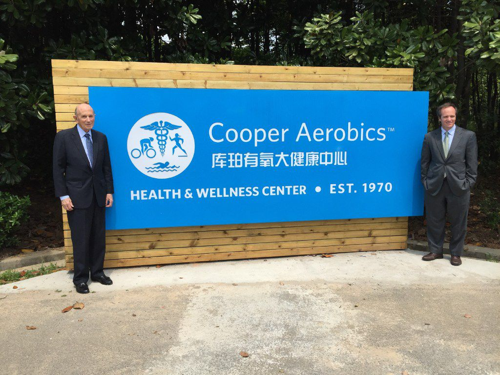 Ken Cooper and his son Tyler Cooper pose with a sign at Cooper Aerobics Health and Wellness Center China