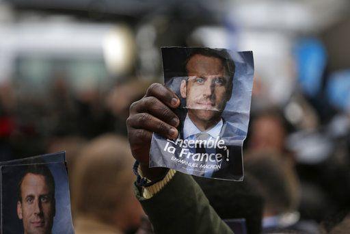 Unos partidistas del candidato francés independista, Emmanuel Macron, levantan su foto en las afueras de su centro de campaña en París. Foto AP.