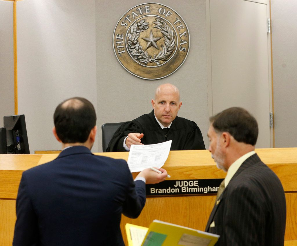 State District Judge Brandon Birmingham listened Tuesday as prosecutor Herschel Woods (left) and defense attorney Steve Miller discussed releasing a man in jail on $1,500 bail — or $150 cash, which the man doesn't have.