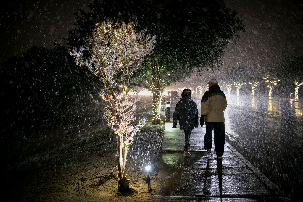 Larry and Licette Wagner walk in the snow on Escarpment Boulevard in Austin, Texas, on Thursday Dec. 7, 2017.