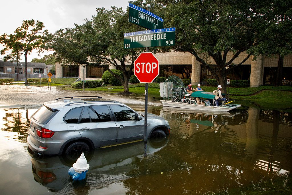 A boat carries a Houston police officer and CenterPoint Energy employees through a flooded street in the Energy Corridor on Sunday, Sept. 3, 2017, in Houston.  The area remains flooded from Hurricane Harvey.