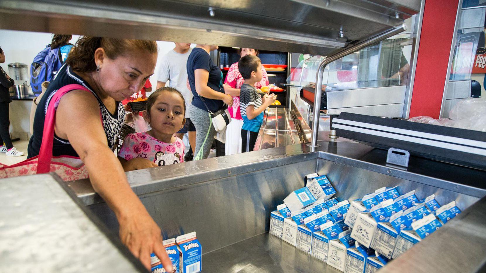 María Vargas (izq.) ayuda a Brianna García con su bebida en el inicio del Programa de Comidas de Verano que fue lanzado el martes en la primaria Herbert Marcus.
