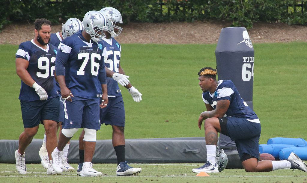 Dallas Cowboys defensive tackle David Irving (95), right, takes a knee as he watches his teammates work out at Dallas Cowboys mandatory minicamp in Frisco, Texas, on Monday, June 12, 2018. (Louis DeLuca/The Dallas Morning News)
